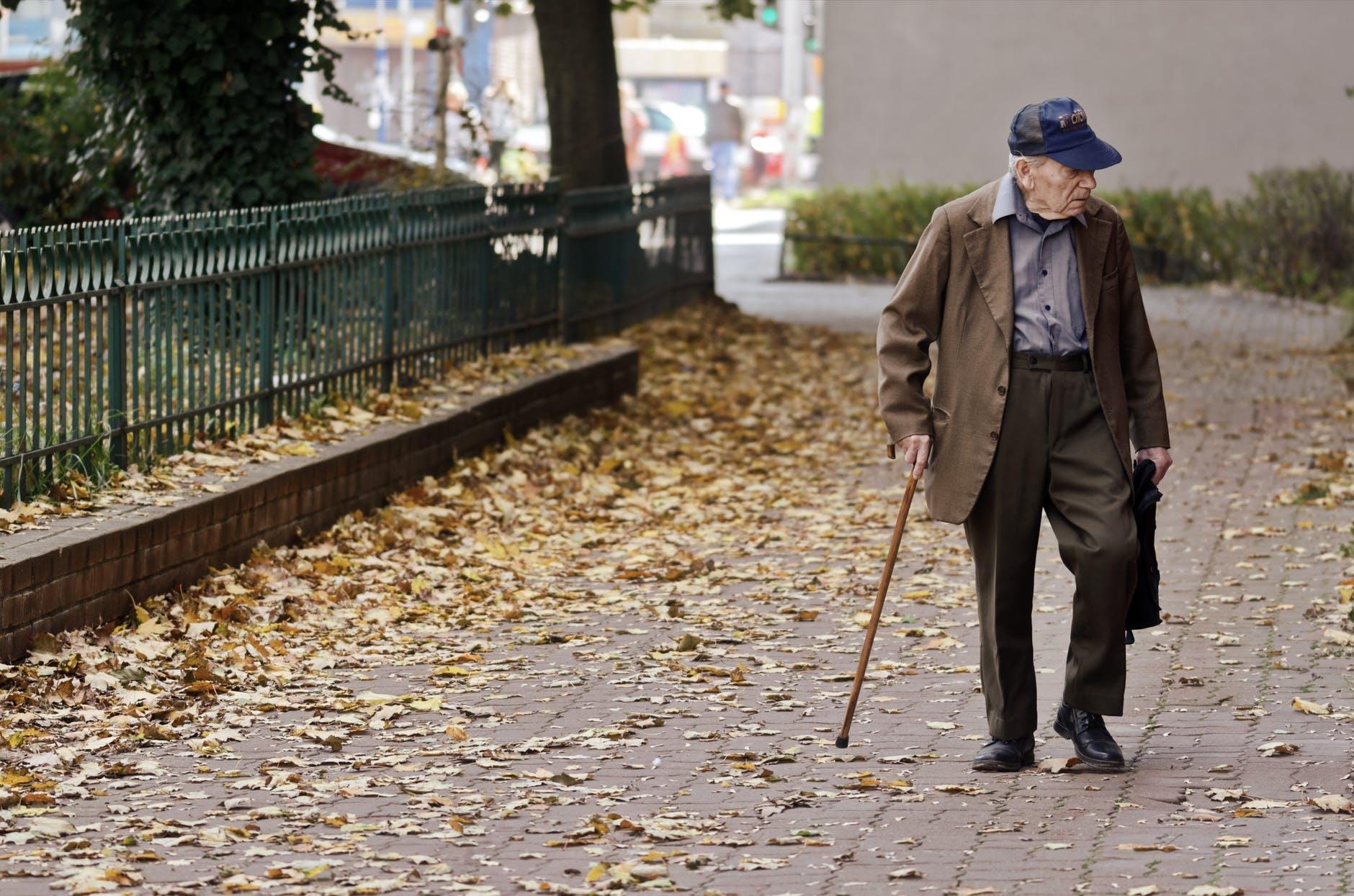 photo of elderly man walking on pavement